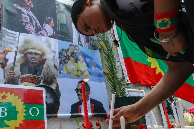A member of the Oromo Ethiopian community in Beirut, Lebanon lights a candle to protest the death of musician and activist Hachalu Hundessa [Anwar Amro/AFP]