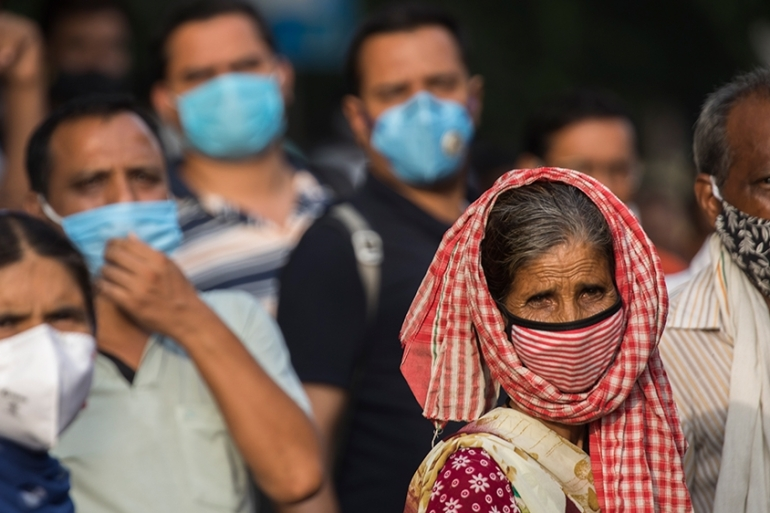 Commuters wearing facemasks wait for their bus after work during a rush hour in New Delhi on July 21 [Xavier Galiana/AFP]