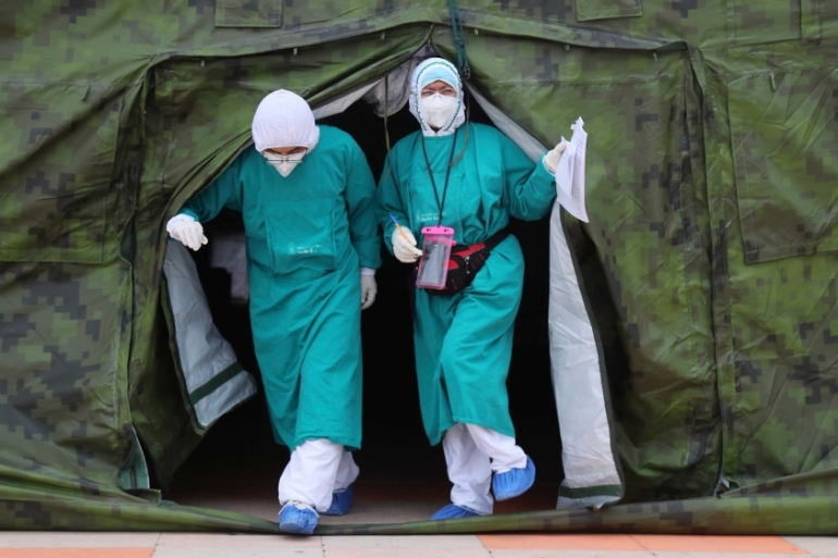 Doctors exiting a tent where people who have tested positive for the new coronavirus are being treated, outside the Seguro Social hospital in Quito, Ecuador [AP Photo/Dolores Ochoa]