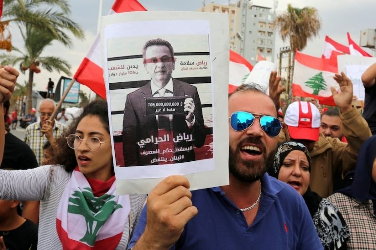 Demonstrators carry Lebanese flags and a poster depicting Lebanon's central bank governor, Riad Salameh, in the southern city of Tyre [File: Aziz Taher/AP]
