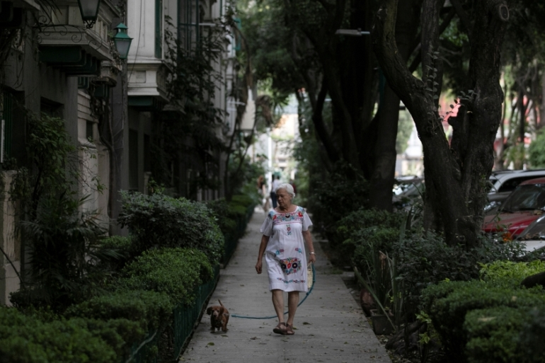 A woman walks with a dog on the street after Mexico's government declared a health emergency in Mexico City, Mexico, whose credit rating has been cut in recent months and the country is in danger of additional declines [File: Carlos Jasso/Reuters]