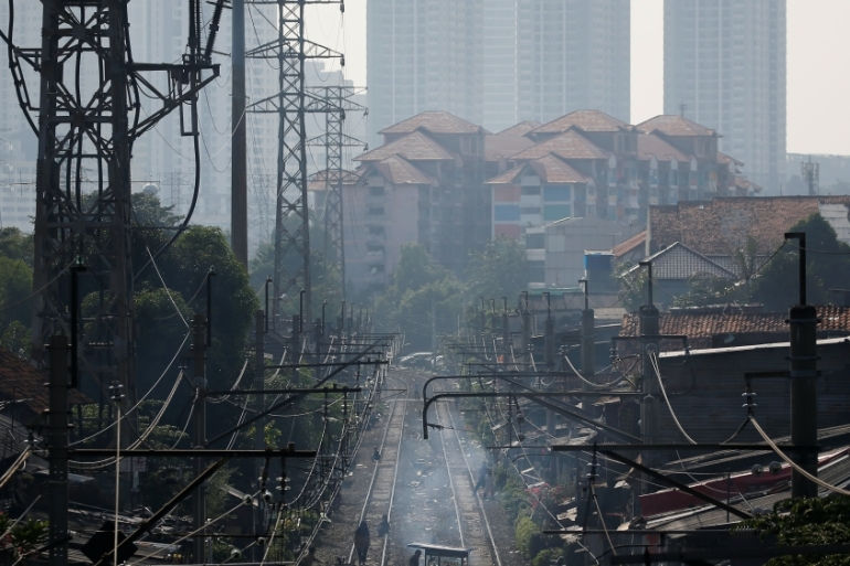 Street vendors push their carriages crossing a railway after the government eased restrictions following the coronavirus outbreak, at a densely populated residential area in Jakarta, Indonesia [File: Willy Kurniawan/Reuters]