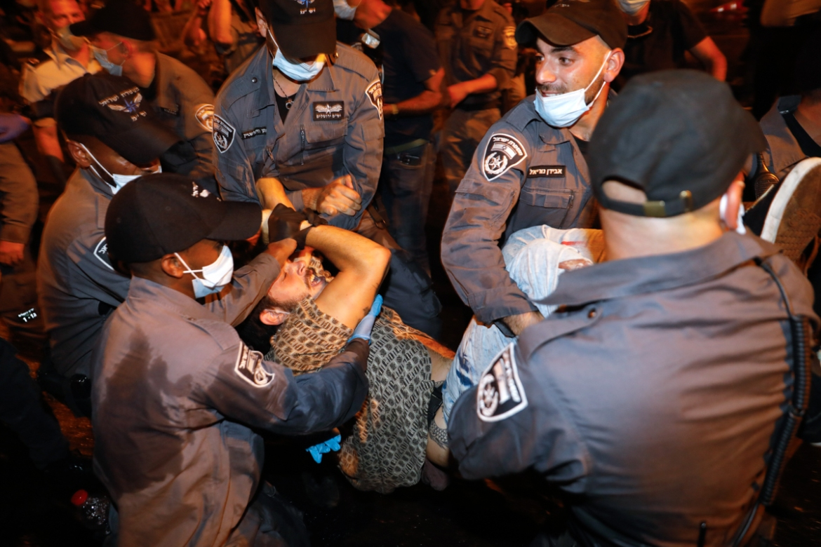 A protester is detained by police during the demonstration. [Menahem Kahana/AFP]