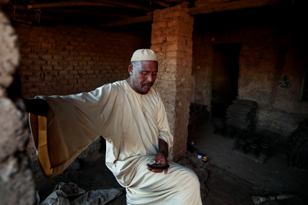 Mutasim al-Jeiry, 50, a potter, sits inside his workshop in an area known as the 'Potters Village' in Alqamayir, Omdurman. The dam 'will stabilise the Nile and we will get less flooding', said al-Jeiry. 'But on the other hand, we will get less clay and less water. Farmers, brick and pottery makers will be seriously affected.' [Zohra Bensemra/Reuters]