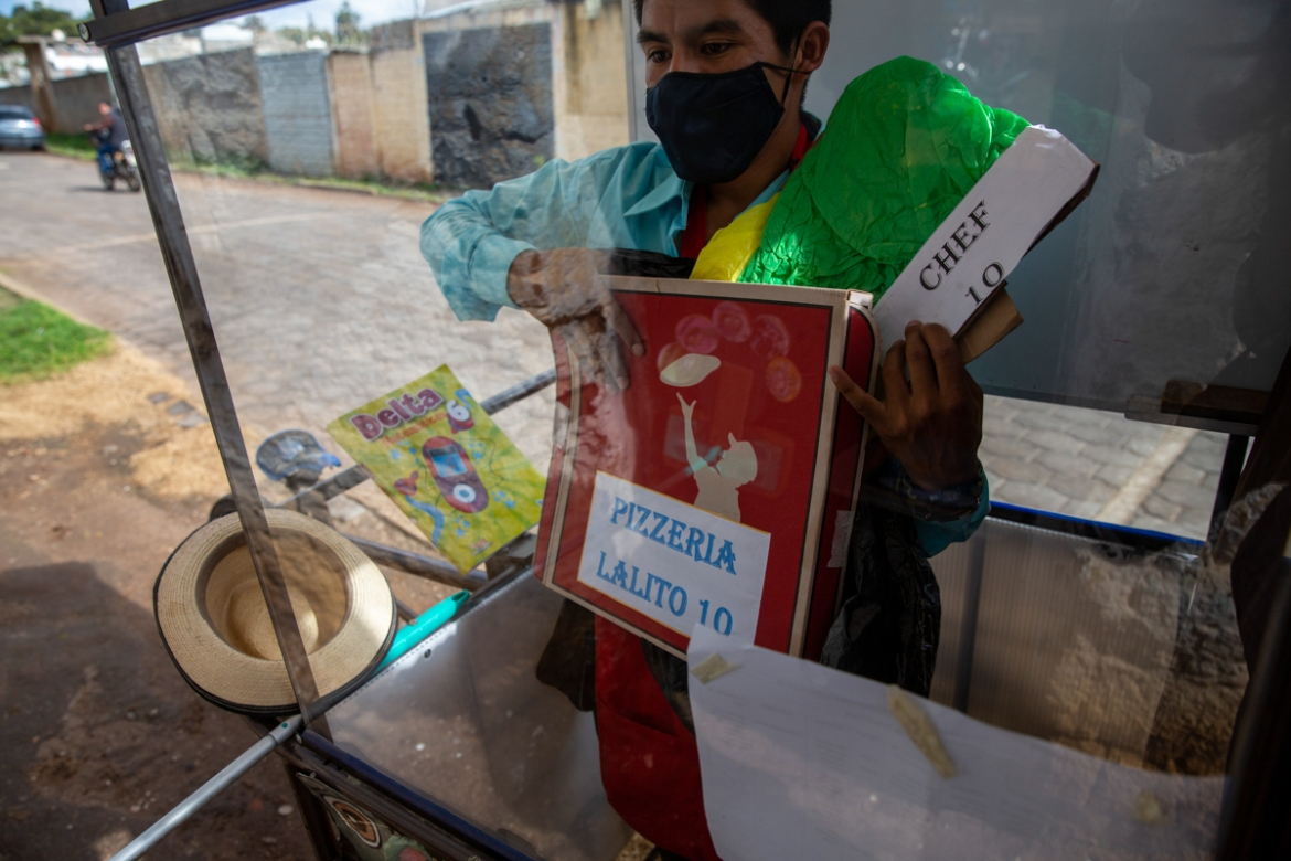 "Standing behind the Plexiglas window of his mobile classroom, Gerardo Ixcoy holds a pizza box as part of a lesson on fractions. ""I tried to get the kids their worksheets, sending instructions via WhatsApp, but they didn't respond,"" Ixcoy said. [Moises Castillo/AP Photo]"