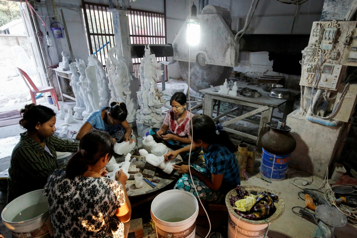 Women who work at a marble workshop, polish marble statues in Sagyin. [Ann Wang/Reuters]