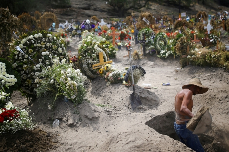 A cemetery worker digs new graves at the Xico cemetery on the outskirts of Mexico City [Edgard Garrido/Reuters]