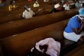 A girl sleeps on a bench at the Cathedral of Port-au-Prince during a mass after temples and places of worship reopened following coronavirus shutdowns in Haiti [File:Andres Martinez Casares/Reuters]