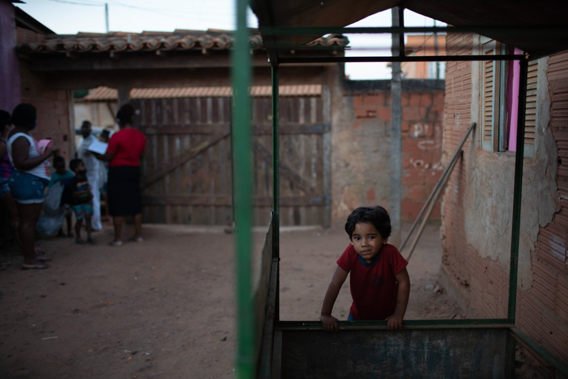 A boy leans on an empty kiosk at Maria Joaquina quilombo in Cabo Frio, on the outskirts of Rio de Janeiro. More than 100 families in the community are trying to weather the coronavirus outbreak. [Silvia Izquierdo/AP Photo]
