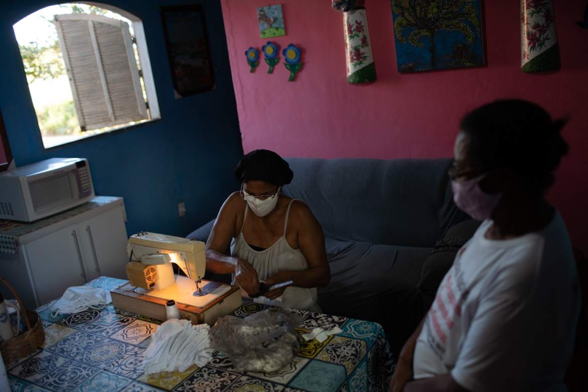 Rosane Da Franca sews protective face masks at her home at the Maria Joaquina quilombo in Cabo Frio, on the outskirts of Rio de Janiero. Rosane is part of a project to make masks and donate them to the residents of the quilombos amid the new coronavirus pandemic. [Silvia Izquierdo/AP Photo]