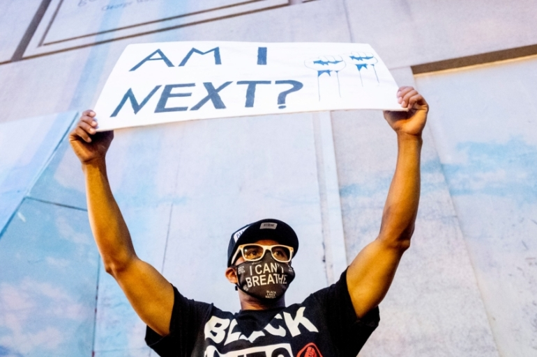 Romeo Ceasar holds a sign during a Black Lives Matter protester on Monday, July 20, 2020, in Portland where protests have continued for more than 50 nights [Noah Berger/AP Photo]