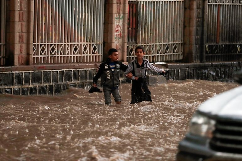 epa08571506 Two Yemeni boys wade and attempt to traverse a flooded street during heavy rainfall in Sana''a, Yemen, 28 July 2020. Heavy rains and associated floods have hit Yemen in the last few days, killing at least 14 people and destroying dozens of houses and roads.  EPA-EFE/YAHYA ARHAB [EPA]