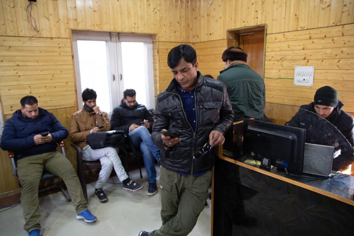 Kashmiri journalists browse the internet on their mobile phones inside the media centre set up by authorities in Srinagar. Indian authorities on March 4 temporarily revoked a ban on social media sites and restored internet access but ban on high-speed 4G internet remains. [Dar Yasin/AP Photo]