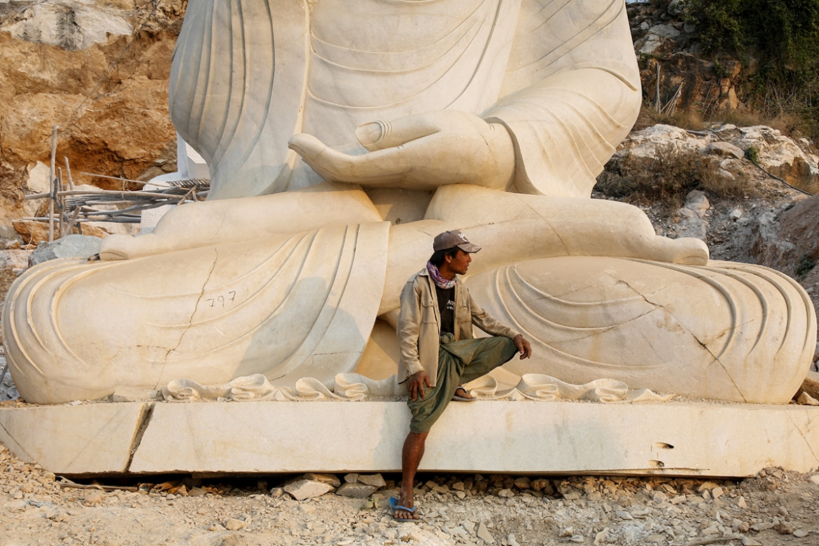 Chin Win, 35 leans on a marble statue of a Buddha as he rests at a marble site where he works. [Ann Wang/Reuters]