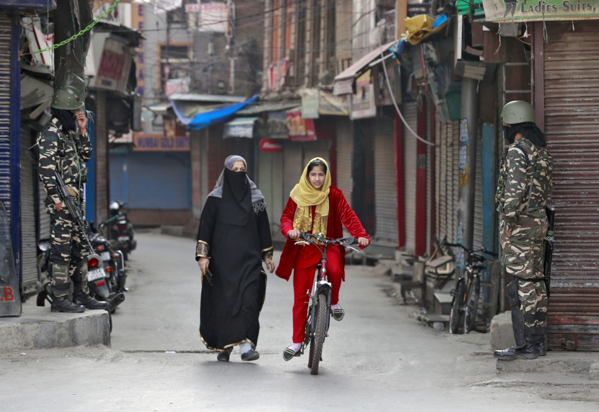 A Kashmir girl rides her bike past Indian security force personnel standing guard in front closed shops in a street in Srinagar, October 30, 2019. [Danish Ismail/Reuters]
