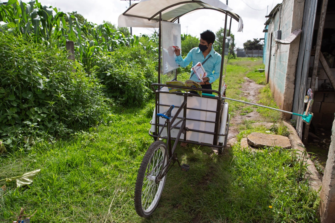 Ixcoy, also known as Lalito 10, invested his savings in an adult tricycle and converted it into a mobile classroom to address the challenges of remote learning in the Santa Cruz del Quiche farming community in Guatemala's western highlands.  [Moises Castillo/AP Photo]
