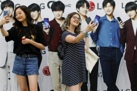 Attendees take selfies with cardboard cutouts at KCON USA, billed as the world's largest Korean culture convention and music festival in Los Angeles on August 10, 2018 [Mike Blake/Reuters]