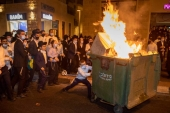 Ultra-Orthodox Jews burn a dumpster during a protest against a lockdown in their neighbourhood due to a coronavirus outbreak [File: Oded Balilty/AP Photo]