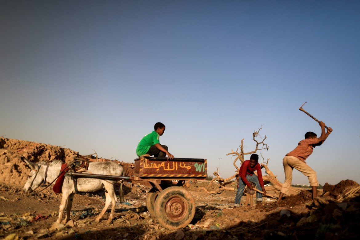 Mazeen, right, 12, collects clay in the 'Potters Village'. [Zohra Bensemra/Reuters]