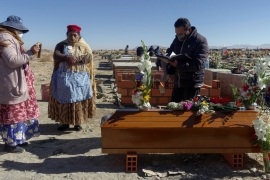 Mourners standing next to the coffin of their relative during a burial in El Alto outskirts of La Paz, Bolivia [David Mercado/Reuters]