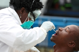 A member of medical staff swabs the mouth of a resident for a medical test, during a nationwide lockdown to try to contain the COVID-19 outbreak, in Alexandra, South Africa, March 31, 2020 [Siphiwe Sibeko/Reuters]