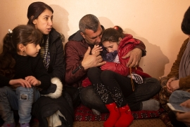 In this February 12, 2020 photo, Malak Saad Dakhel, an 11-year-old Yazidi, is overwhelmed by journalists and well-wishers as her family tries to comfort her after her escape from Syria [File: Maya Alleruzzo/AP]