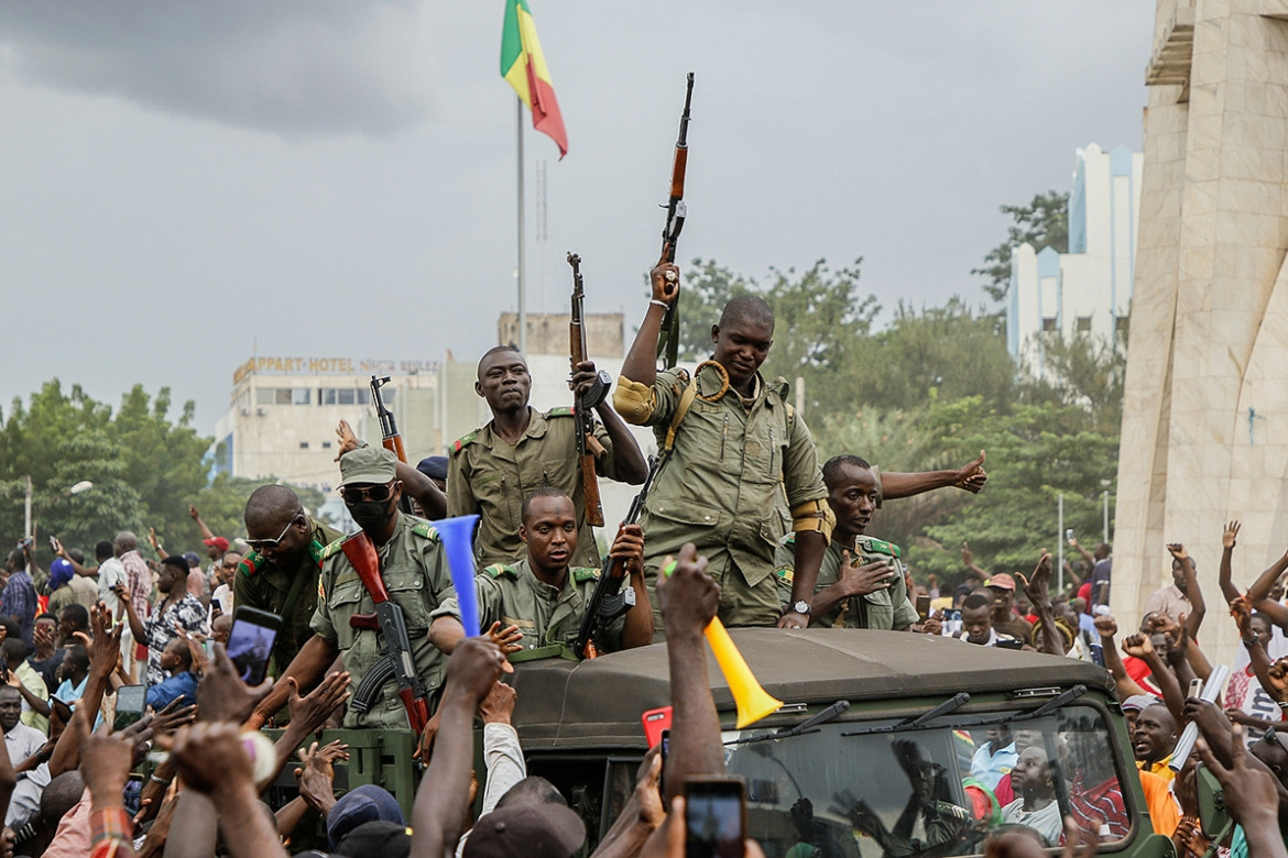 People cheer as soldiers enter the streets of Bamako. [Moussa Kalapo/EPA]