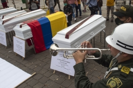 A policeman plays a trumpet next to a set of coffins placed as part of a protests in Medellin against the violence in Colombia, where several massacres have happened during the past days [Joaquin Sarmiento/AFP]