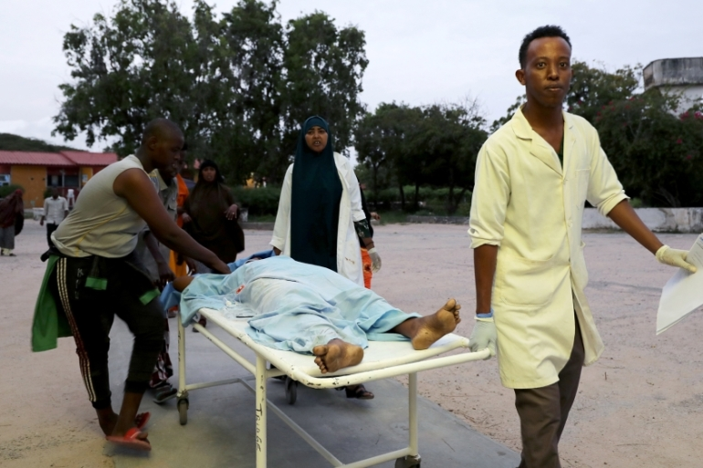 Paramedics and civilians carry an injured person on a stretcher at Madina hospital after a blast at the Elite Hotel in Lido beach in Mogadishu [Feisal Omar/Reuters]