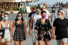 People wear masks as they walk on the street following a government decree that face coverings must be worn between 6 p.m. and 6 a.m. in areas close to bars and pubs and where gatherings are more likely, due to the coronavirus disease (COVID-19) outbreak, in Naples, Italy August 17, 2020. REUTERS/Ciro De Luca [Reuters]