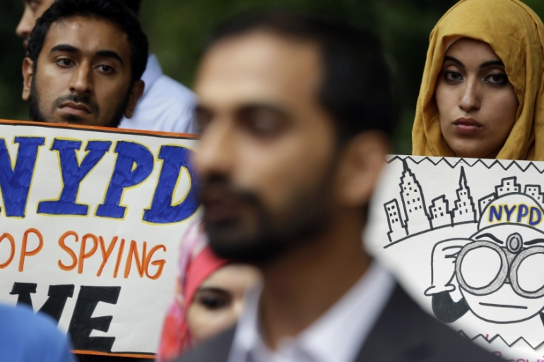 People hold signs while attending a rally to protest the New York Police Department's surveillance tactics near its headquarters in New York on August 28, 2013 [AP/Seth Wenig]