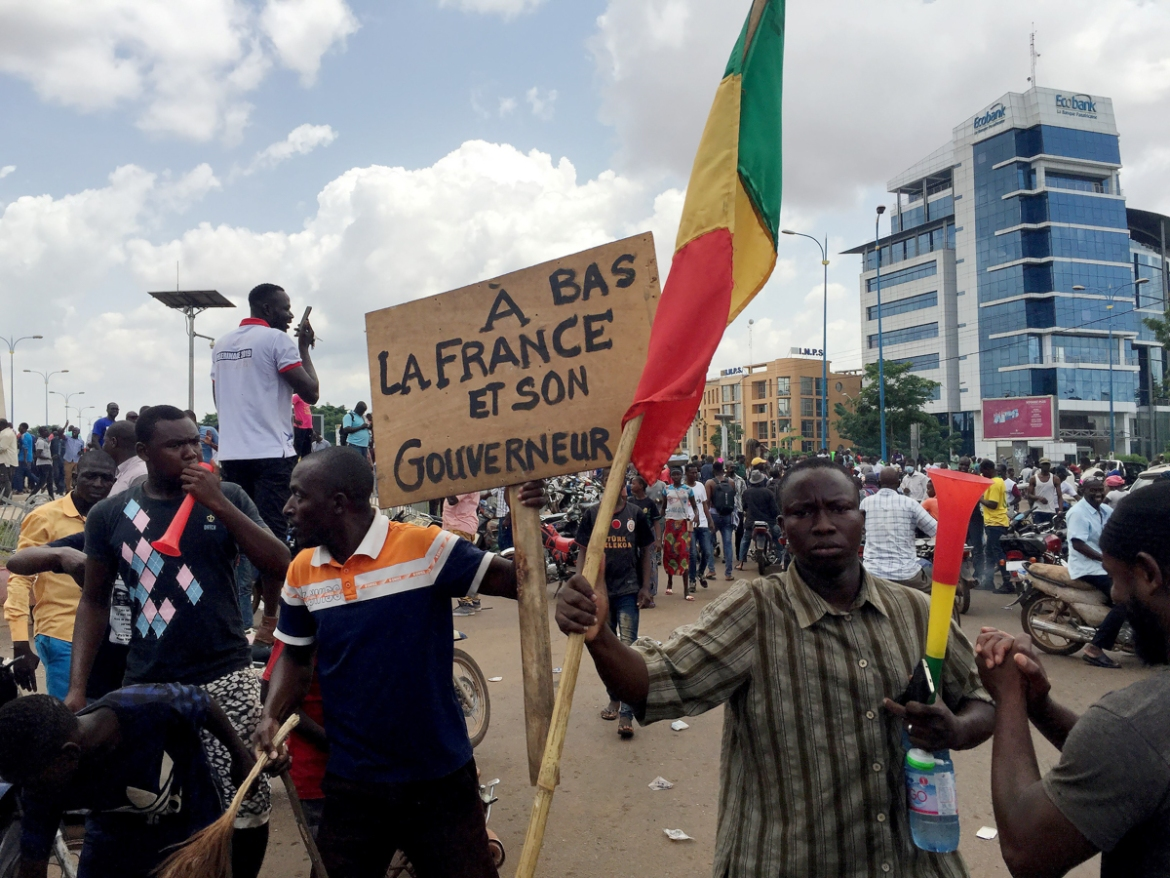 Opposition supporters react to the news of a possible mutiny of soldiers in the military base in Kati, the sign reads: 'Down with France and its governor.' [Rey Byhre/Reuters]