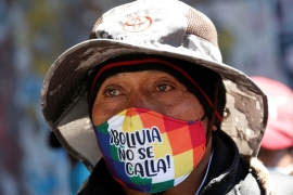 A protester wearing a face mask reading 'Bolivia does not shut up' during a rally demanding Bolivia's President Jeanine Anez's resignation, in El Alto, on the outskirts of La Paz [David Mercado/Reuters]
