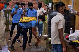 School children wearing masks wash their hands and get their temperatures checked as they arrive to appear for exams in India [File: R S Iyer/AP]