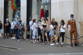 "People with face masks queue as they wait to get in the Louis Vuitton shop on the Champs Elysee avenue in Paris, Saturday, Aug. 15, 2020. Paris extended the areas of the city where pedestrians will be obliged to wear masks starting Saturday morning after health officials said that the coronavirus is ""active"". The Champs-Elysees Avenue and the neighbourhood around the Louvre Museum are among zones where masks will be obligatory. (AP Photo/Kamil Zihnioglu) [The Associated Press]"