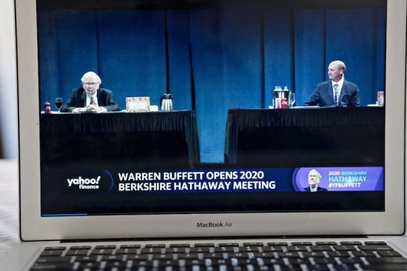 Warren Buffett, chairman and chief executive officer of Berkshire Hathaway Inc, left, speaks as Greg Abel, chairman and chief executive officer of Berkshire Hathaway Energy Co, right, listens during the virtual Berkshire Hathaway annual shareholders meeting in May [File: Andrew Harrer/Bloomberg]