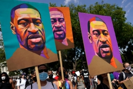 People carry posters bearing George Floyd's face as they march from the Lincoln Memorial to the Martin Luther King Jr Memorial during the March on Washington in August 2020 [Carolyn Kaster/AP]