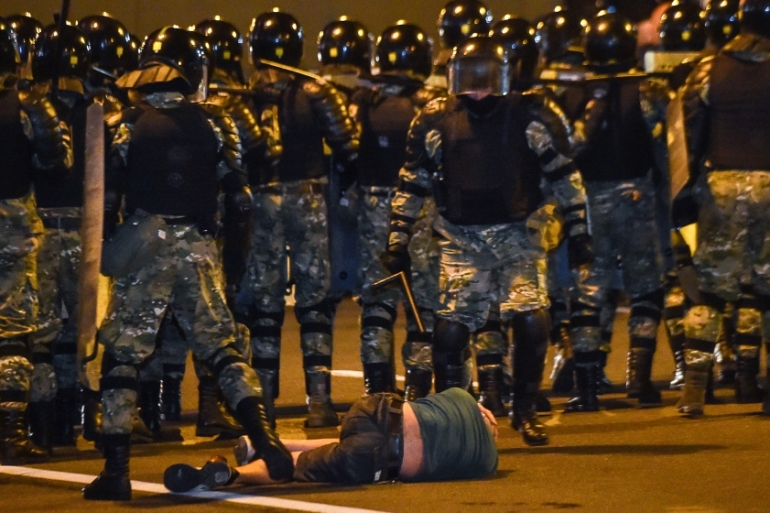 A man lies on the ground in front of riot police during a protest in Minsk [Sergei Gapon/AFP]