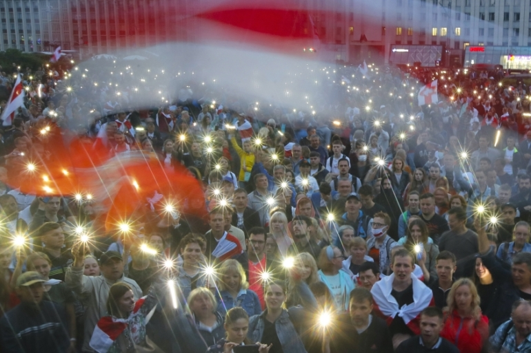Belarusian opposition supporters light phones  and wave  flags during a protest rally at Independent Square in Minsk, Belarus on August 19, 2020 [AP Photo/Dmitri Lovetsky]