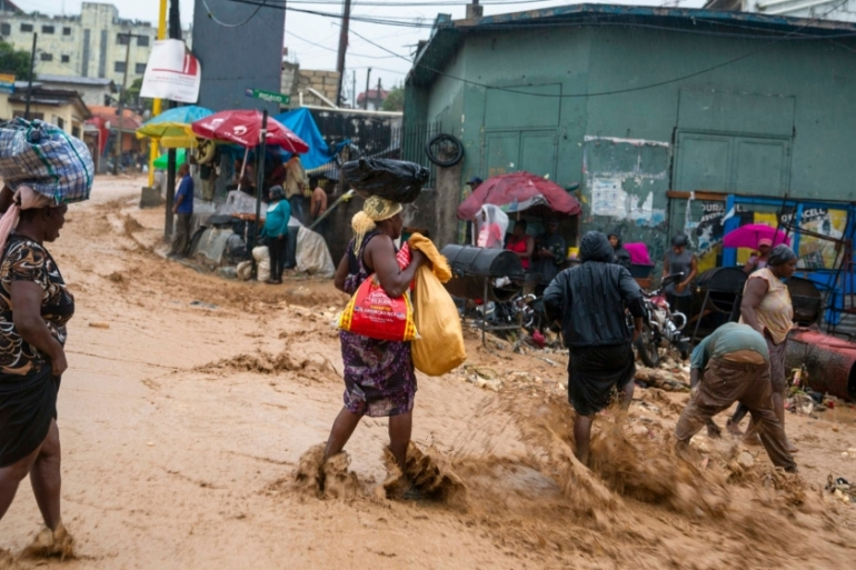 Street vendors cross a flooded street during Tropical Storm Laura in Port-au-Prince, Haiti [Dieu Nalio Chery/AP Photo]