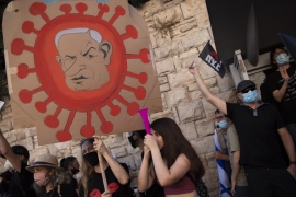 A protester holds a sign depicting Prime Minister Benjamin Netanyahu during a demonstration outside his residence in Jerusalem, on July 31, 2020 [AP/Oded Balilty]