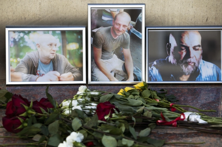 Flowers are placed by portraits of slain journalists Alexander Rastorguyev, Kirill Radchenko and Orkhan Dzhemal at the Russian Journalists' Union in Moscow on August 1, 2018 [File: AP/Pavel Golovkin]