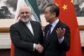 China's Foreign Minister Wang Yi shakes hands with his Iranian counterpart Mohammad Javad Zarif during a meeting in Beijing, China on December 31, 2019 [Noel Celis/Pool Photo via AP]