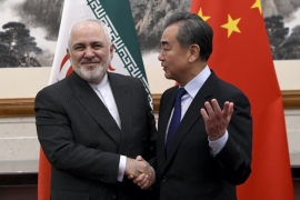 China's Foreign Minister Wang Yi, right, shakes hands with Iran's Foreign Minister Mohammad Javad Zarif [Noel Celis/AP]