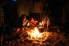 A family in Gaza prepares a meal over a fire amid the fuel shortages caused by Israel's siege [Ashraf Amra/Al Jazeera]