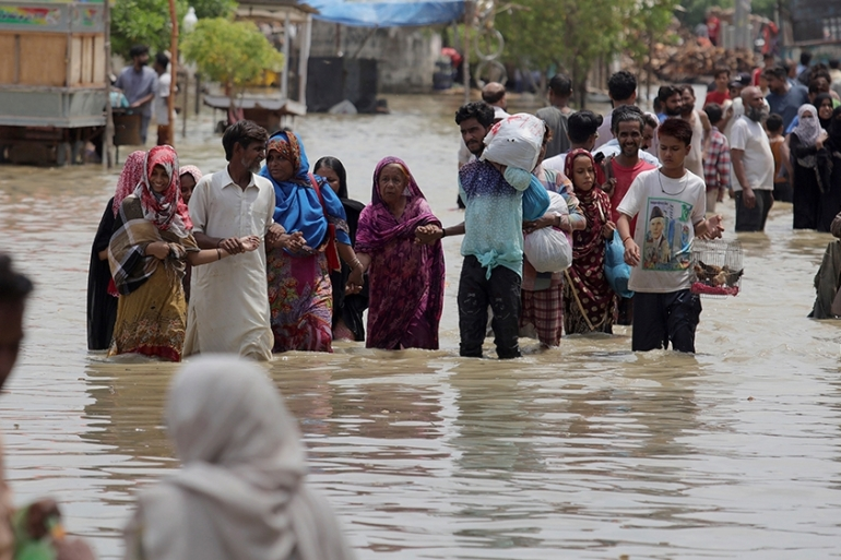 Local residents navigate through a flooded area caused by heavy rainfall in Karachi [Fareed Khan/AP]