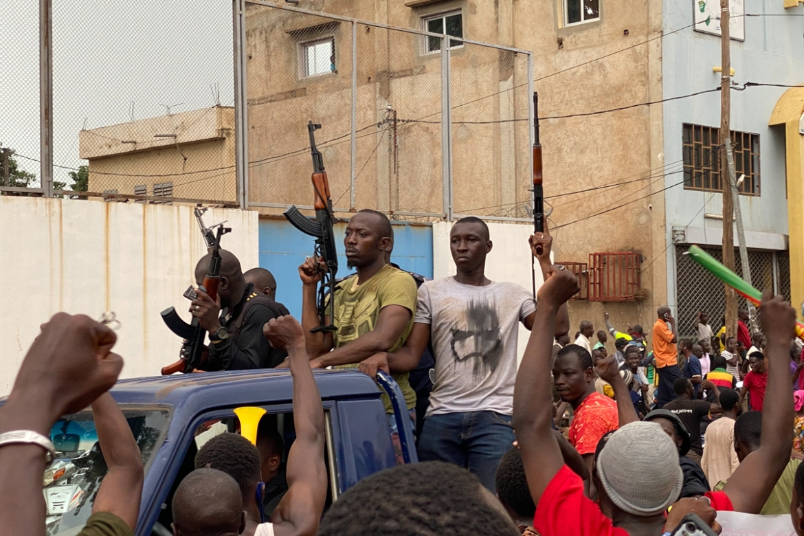 Malian soldiers in civilian clothes are cheered on as they arrive at Bamako's Independence Square. [Malik Konate/AFP]