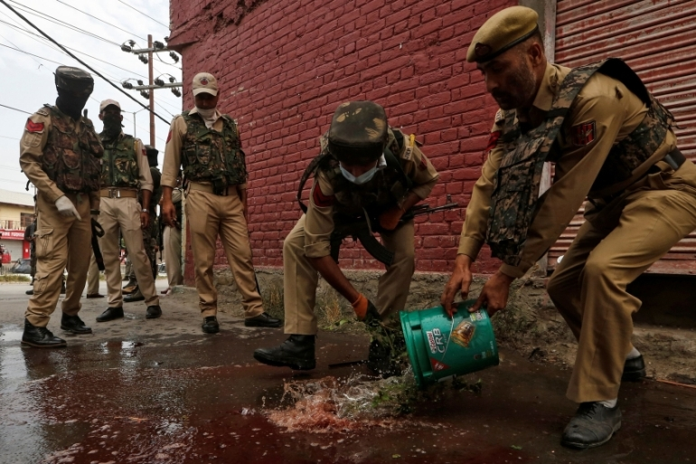 Indian police clean the scene of an attack on security personnel by suspected rebels in Srinagar [Danish Ismail/Reuters]