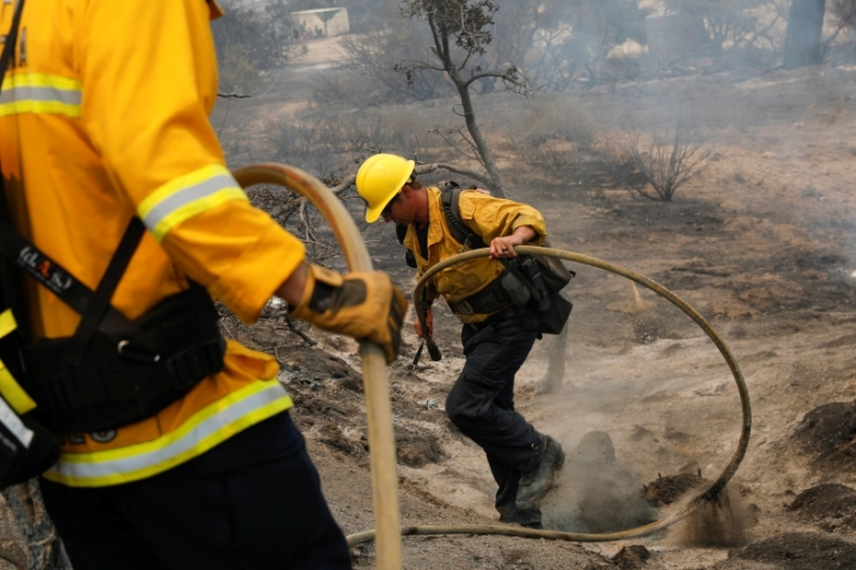 Firefighters extinguish hot spots as a fast-moving wildfire, called the Lake Fire, burns in a mountainous area of Angeles National Forest north of Los Angeles, California in the United States [Patrick T Fallon/Reuters]