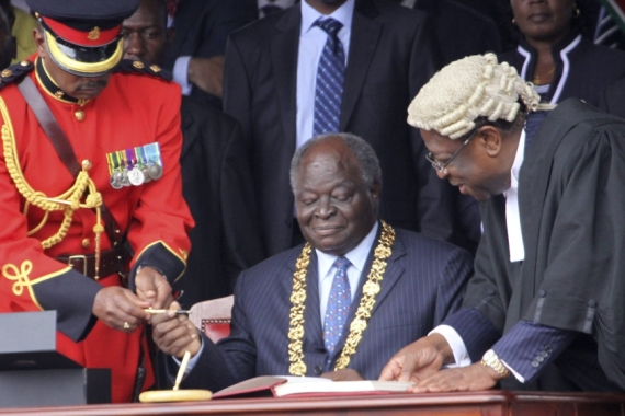 Kenya's then President Mwai Kibaki is seen as he prepares to sign the new constitution into law, at Uhuru Park in Nairobi, Kenya, August 27, 2010 [AP Photo/Khalil Senosi]